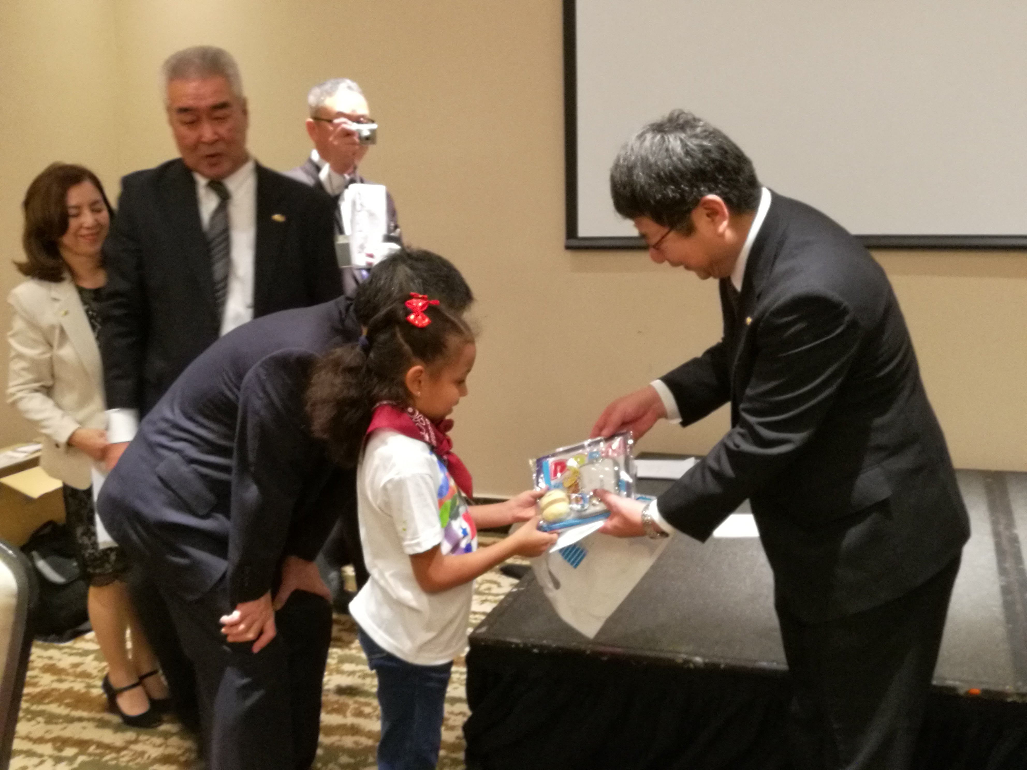 Deputy Mayor of Imabari, Mr. Hiroshi Ochi, giving a commemorative gifts to the students of primary school of Panama.